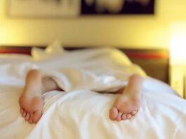 femme dormant dans un lit les pieds à l'air